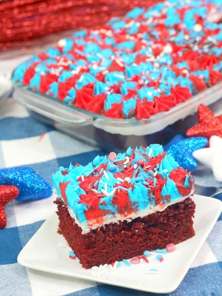 slice of red white and blue cake Red velvet cake on white plate with the full 13x9 cake in the background
