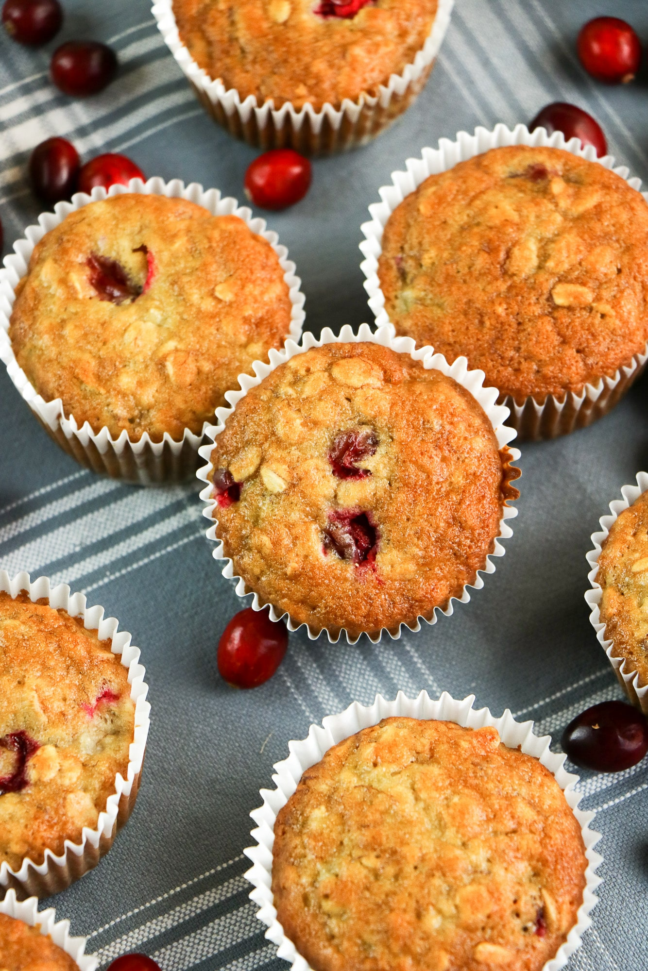 golden cranberry banana muffins on grey and white towel