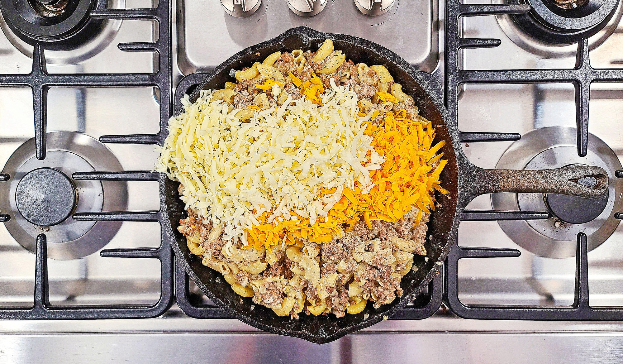 macaroni and cheese with shredded cheese in cast iron skillet
