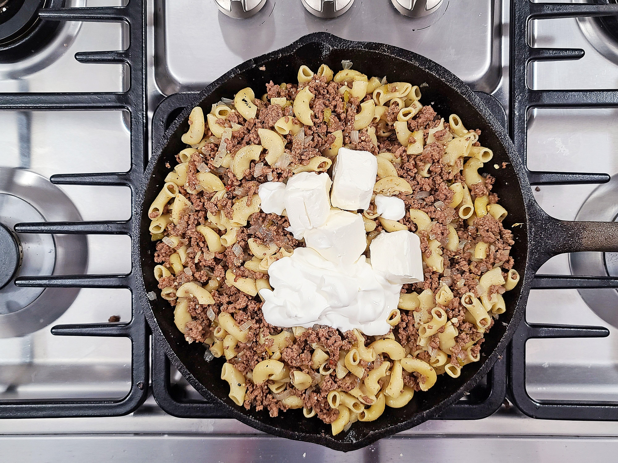 macaroni, ground beef and cream cheese in cast iron skillet