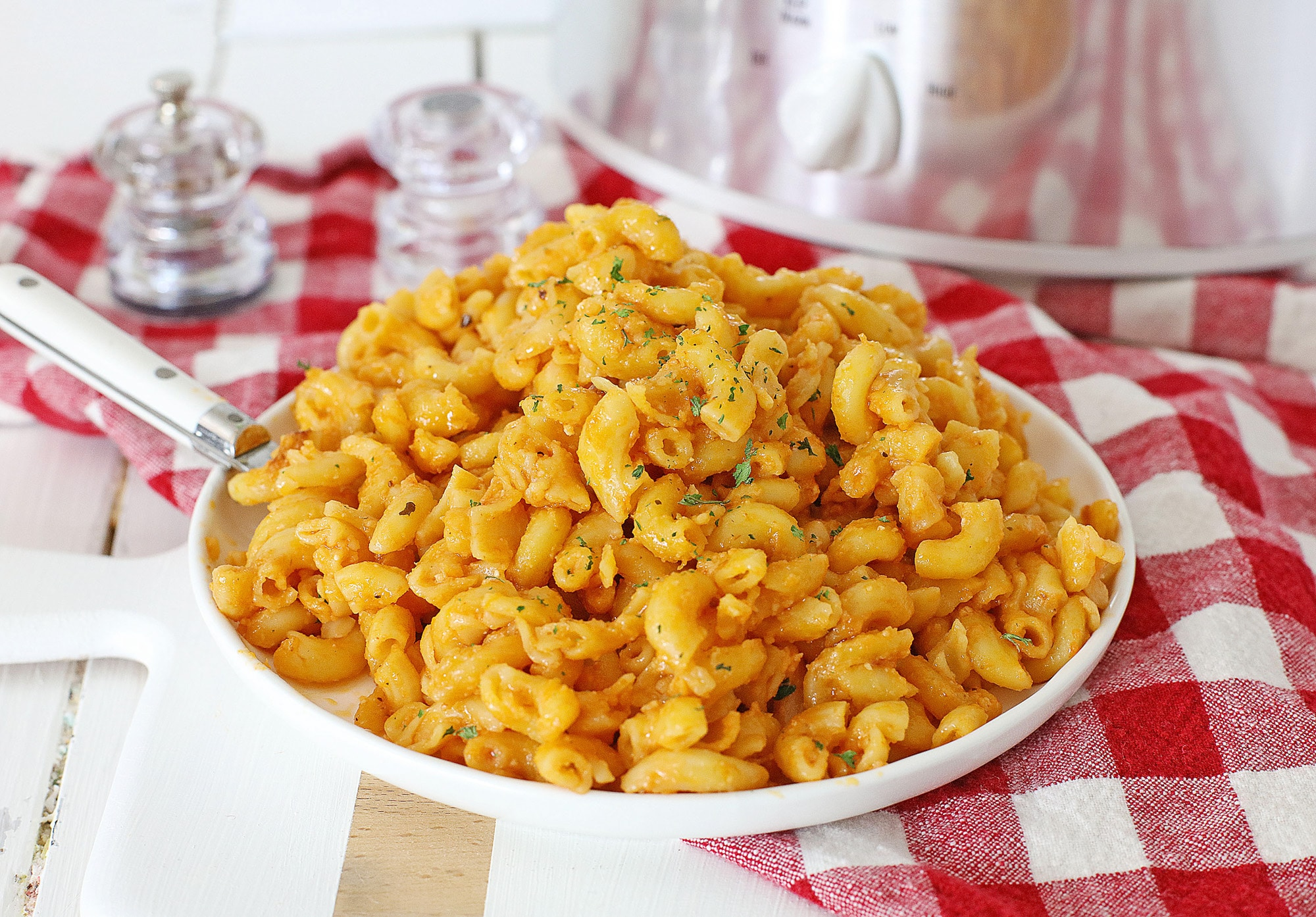 tomato mac and cheese on white plate on top of a red checkered table cloth