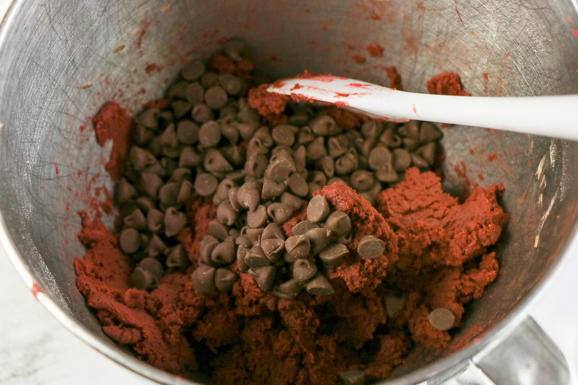 red velvet chocolate chip cookie dough in mixing bowl