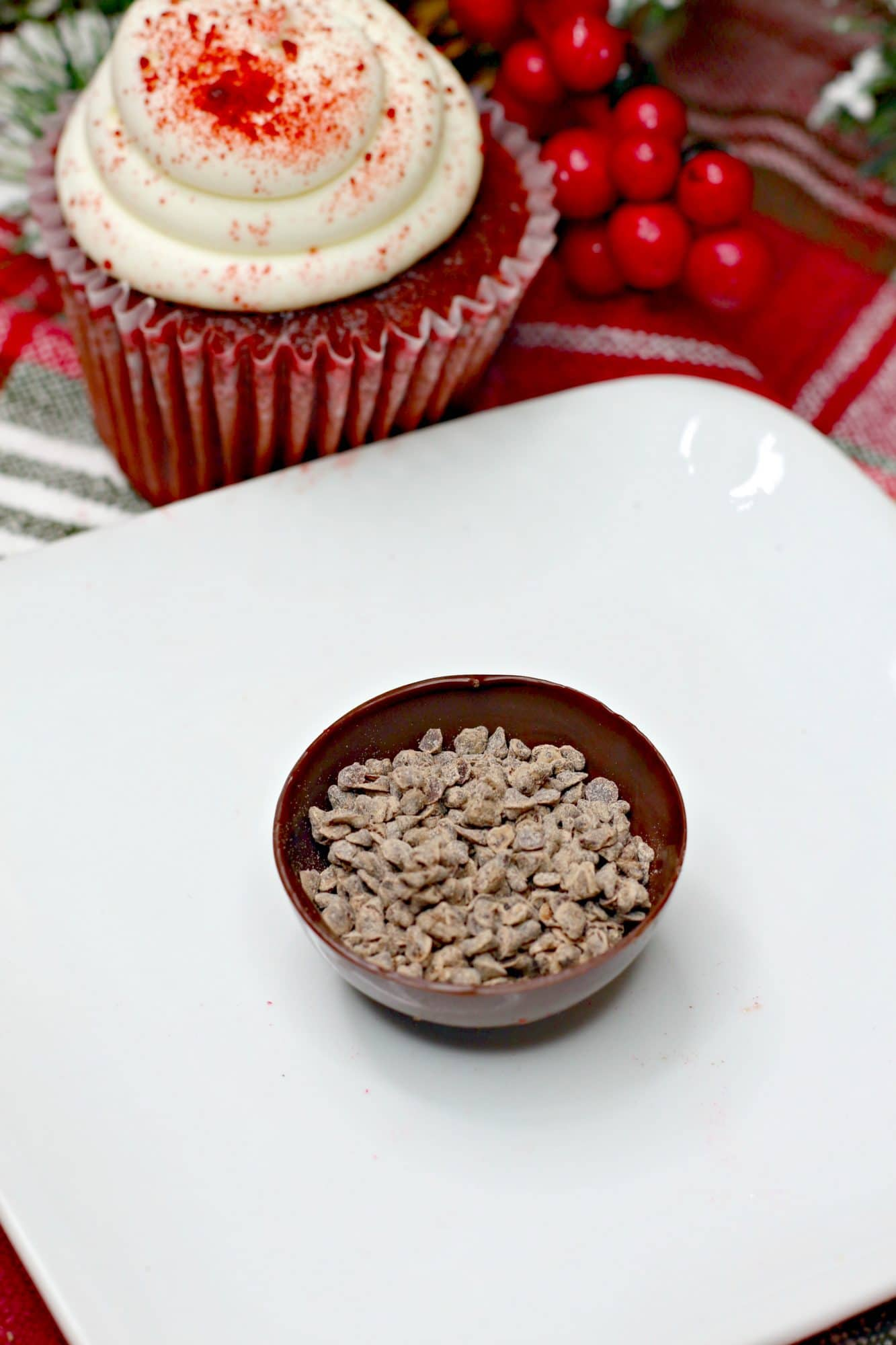 recipe for hot chocolate bombs showing red velvet hot chocolate bombs on white plate with cocoa powder filling