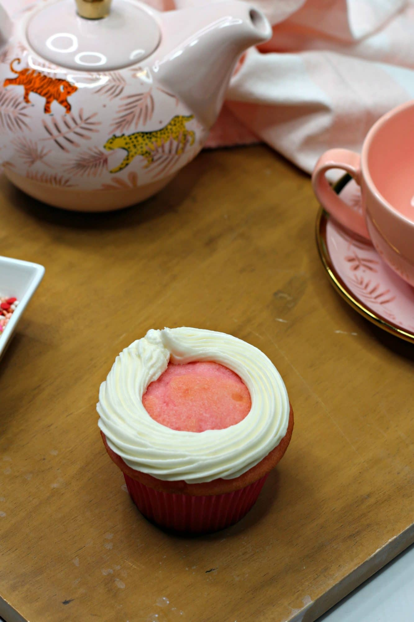 pink cupcake with white frosting outline around the edge
