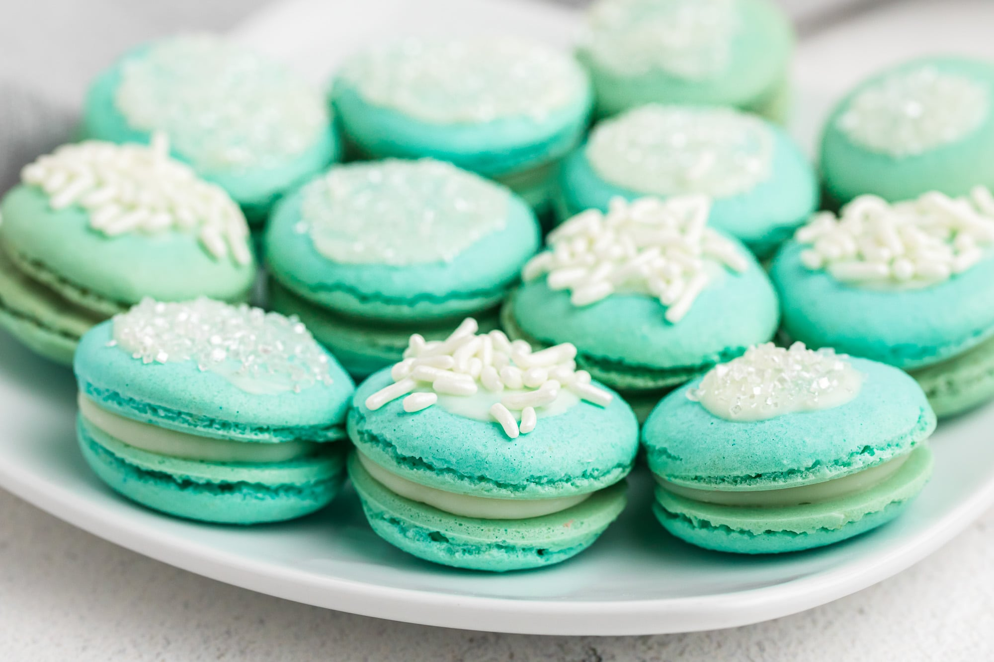 fancy decorated blue macaron cookies on white plate