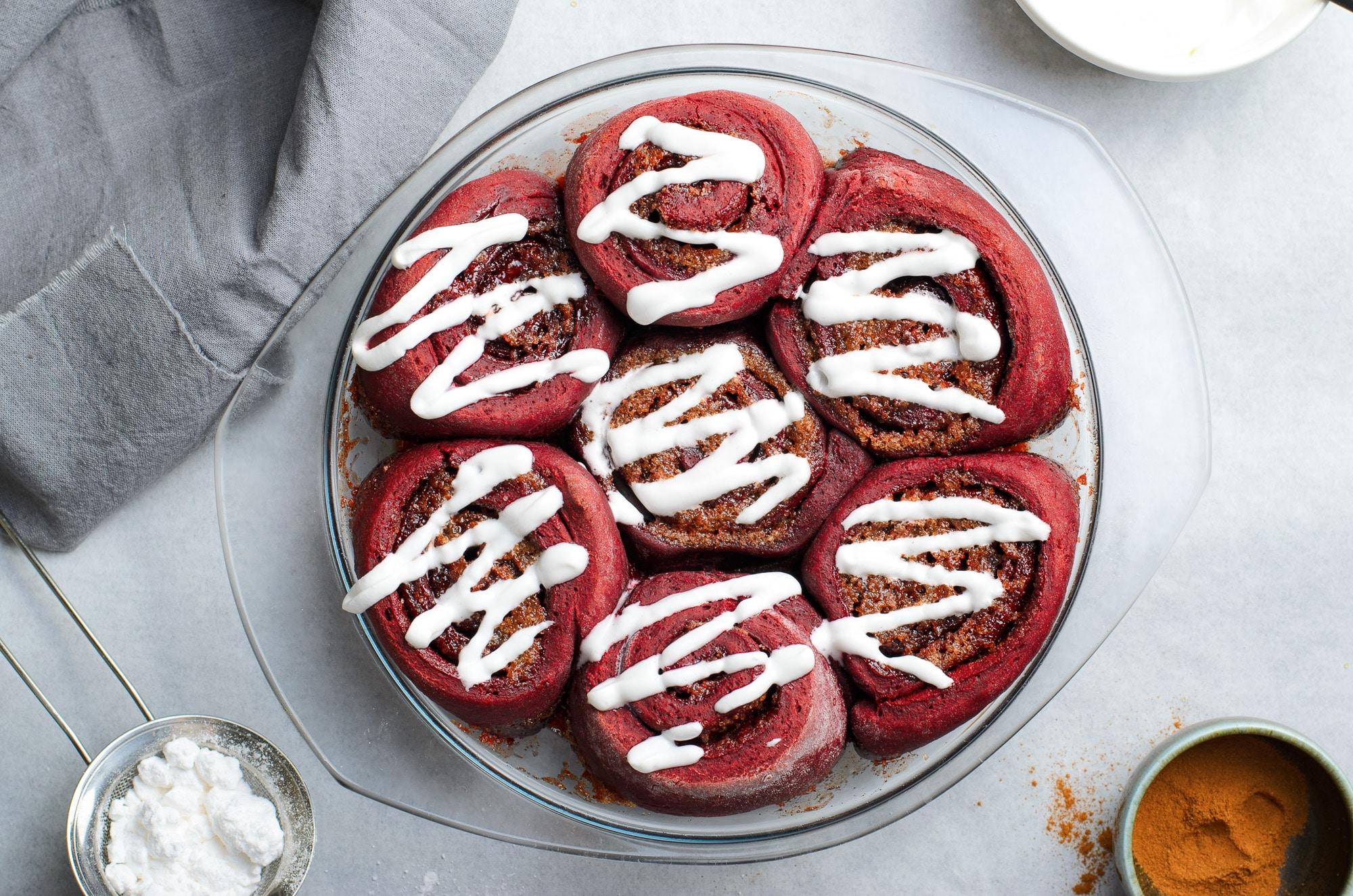 red velvet cinnamon rolls in glass baking dish