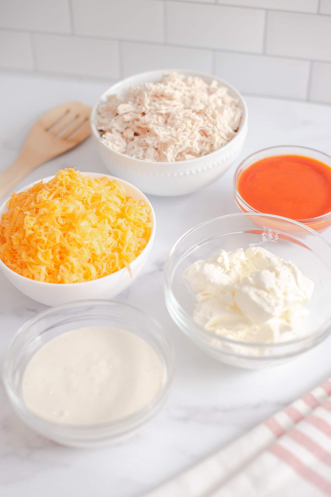 franks buffalo chicken dip ingredients in clear ingredient bowls
