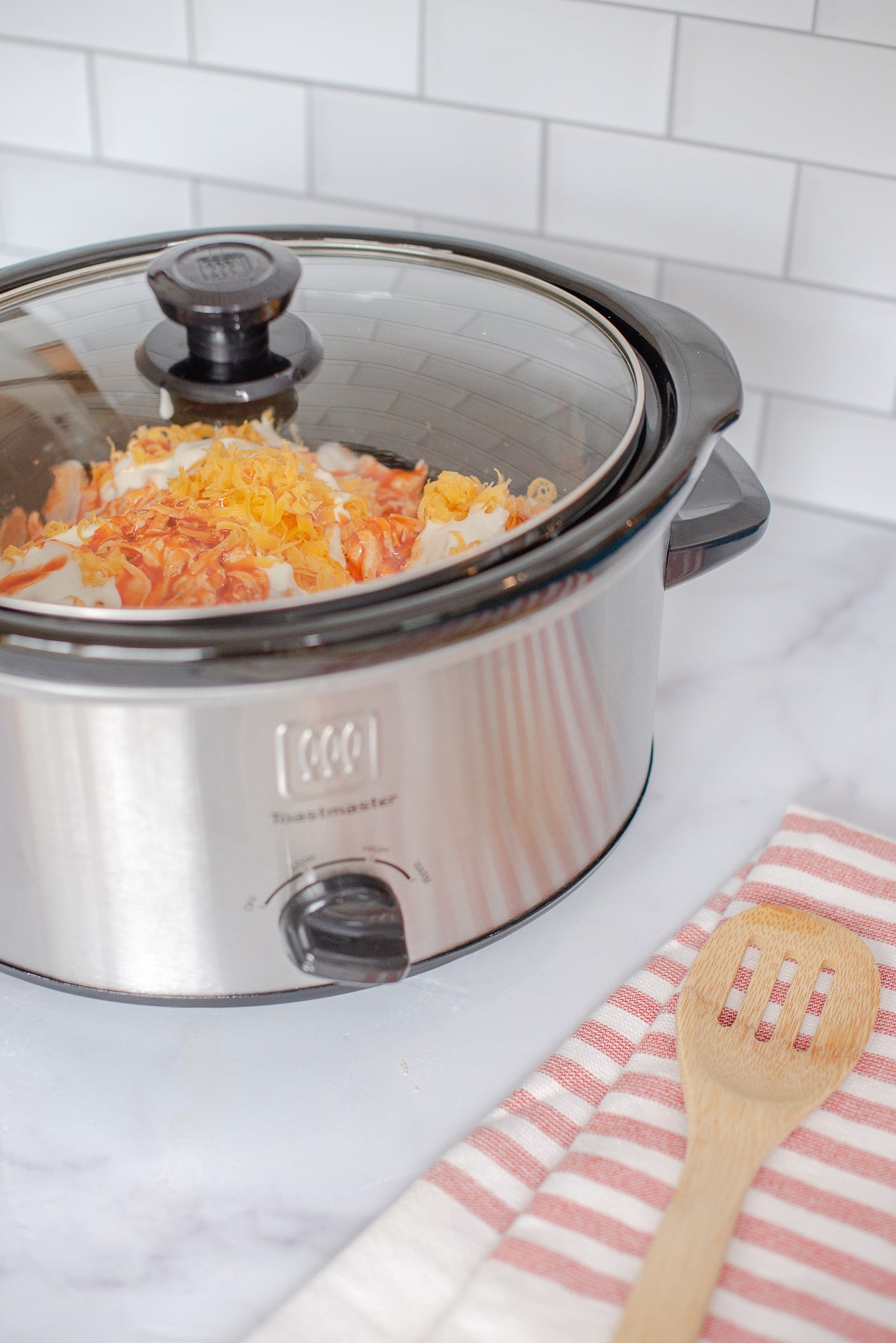crockpot with lid on it and buffalo chicken dip inside