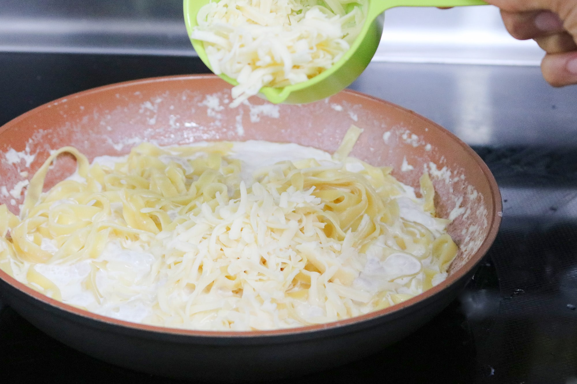adding cheese to cream and noodles in saucepan