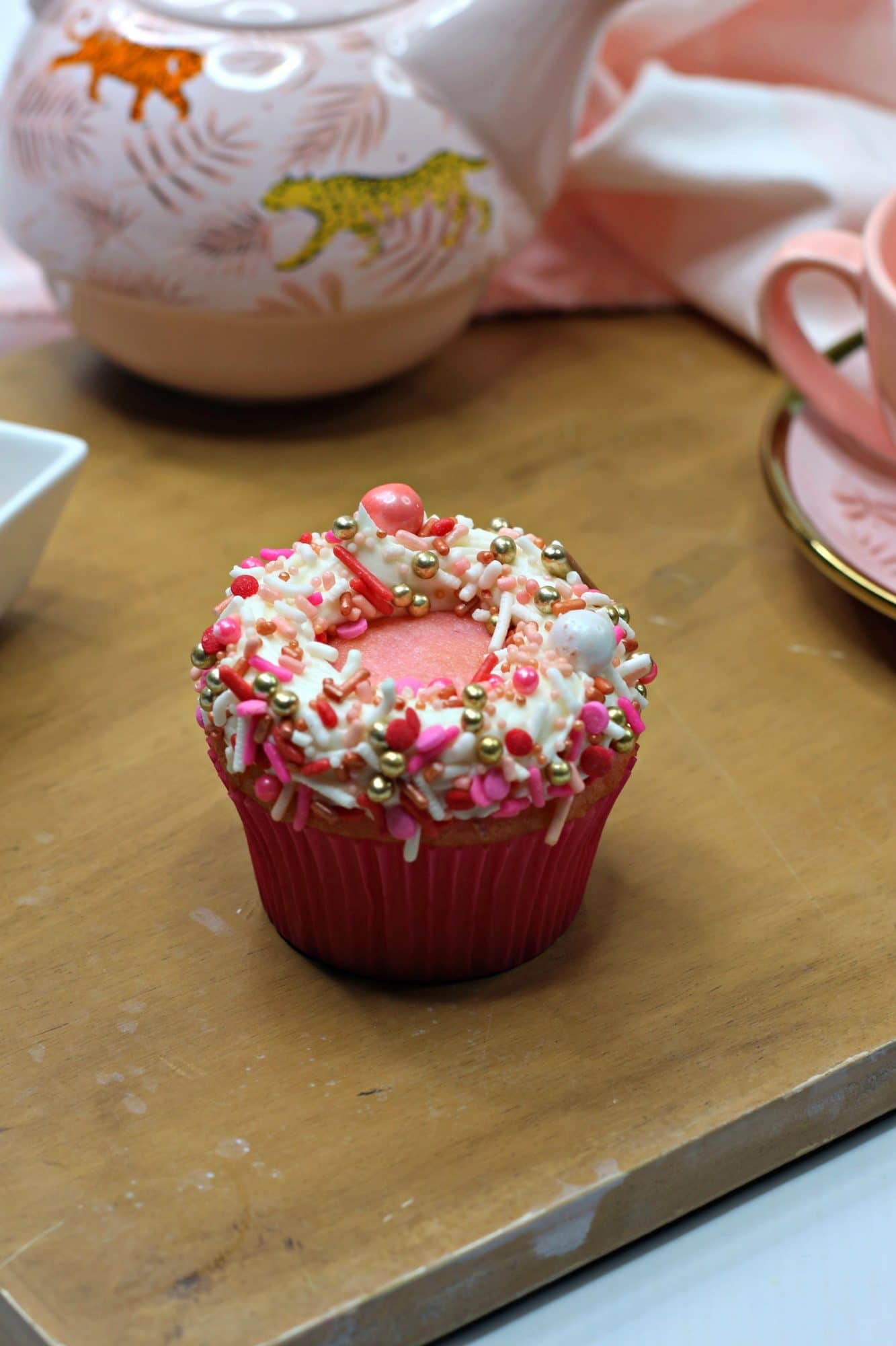pink cupcake with white frosting and sprinkles