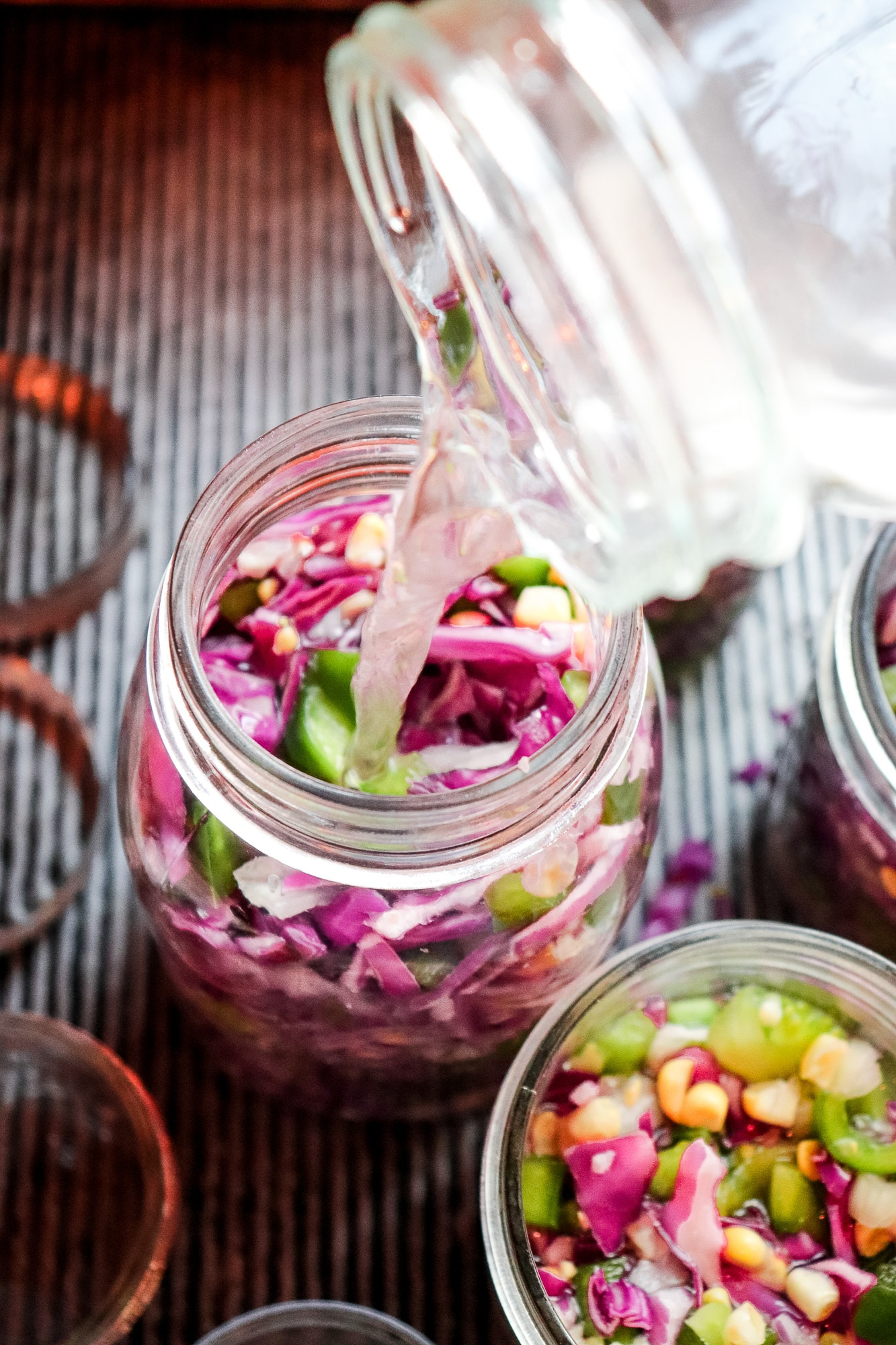 pouring brine water into jars to ferment vegetabls