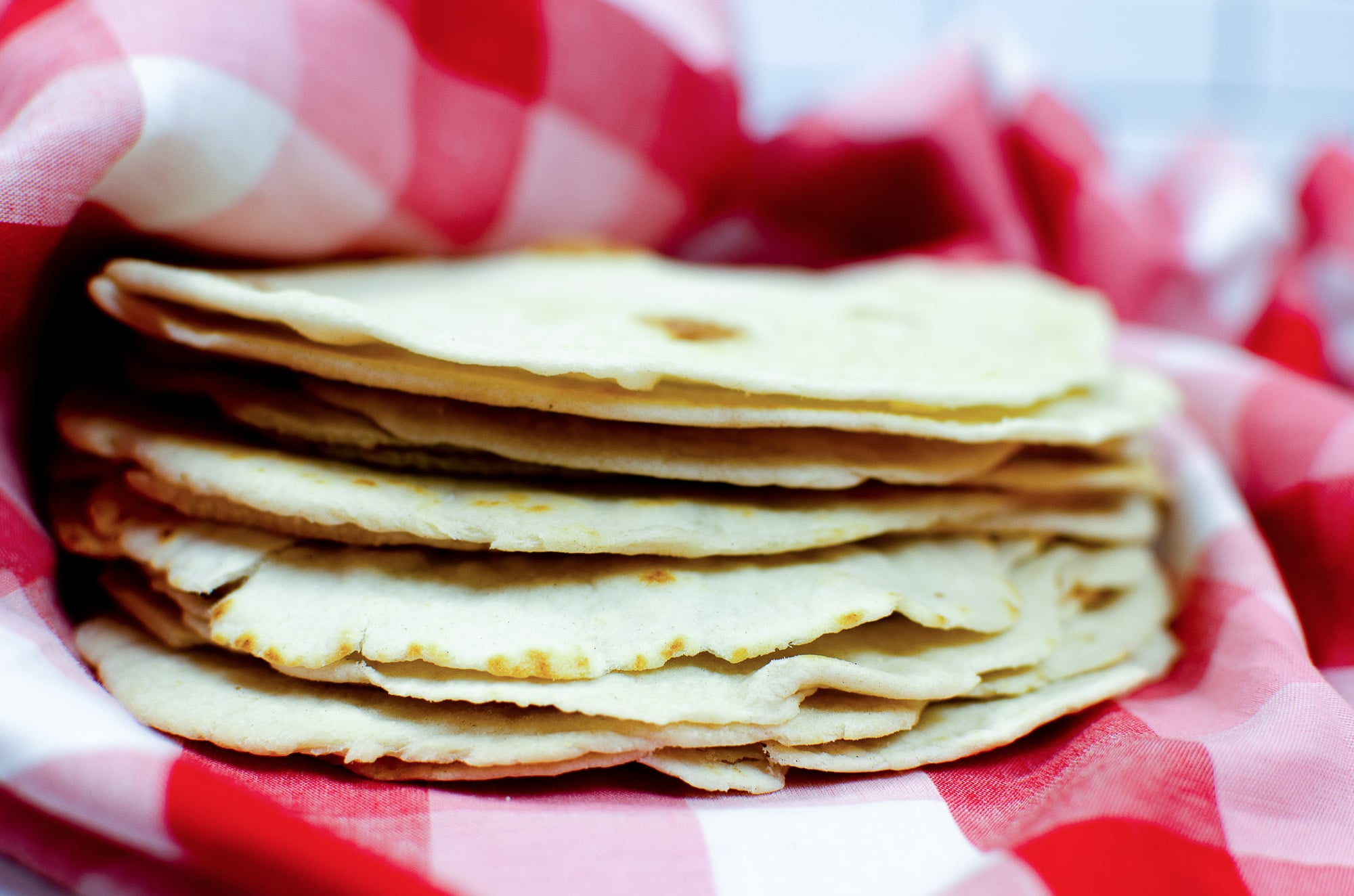 flour tortillas in red and white towel