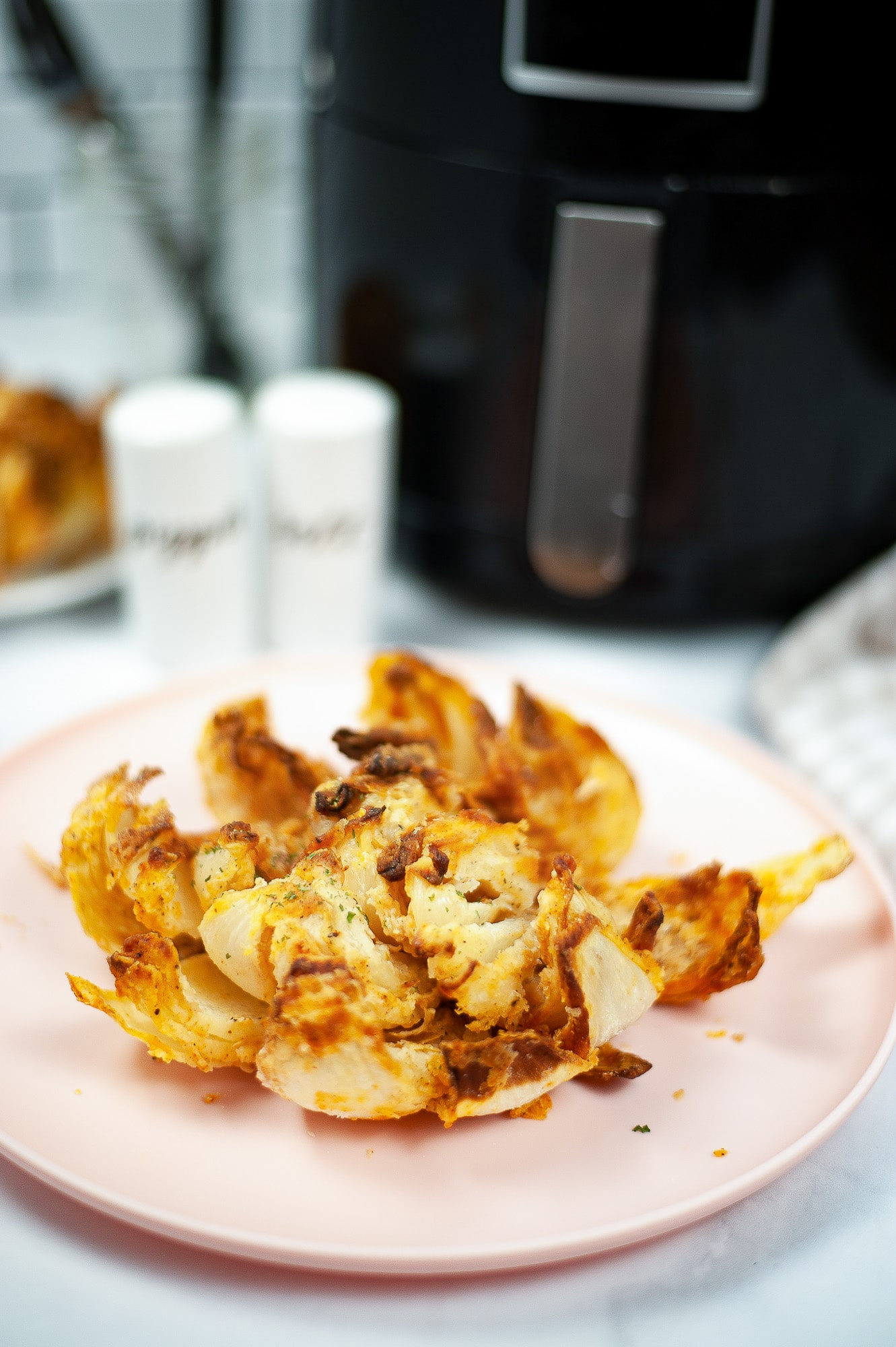 air fried blooming onion on pink plate