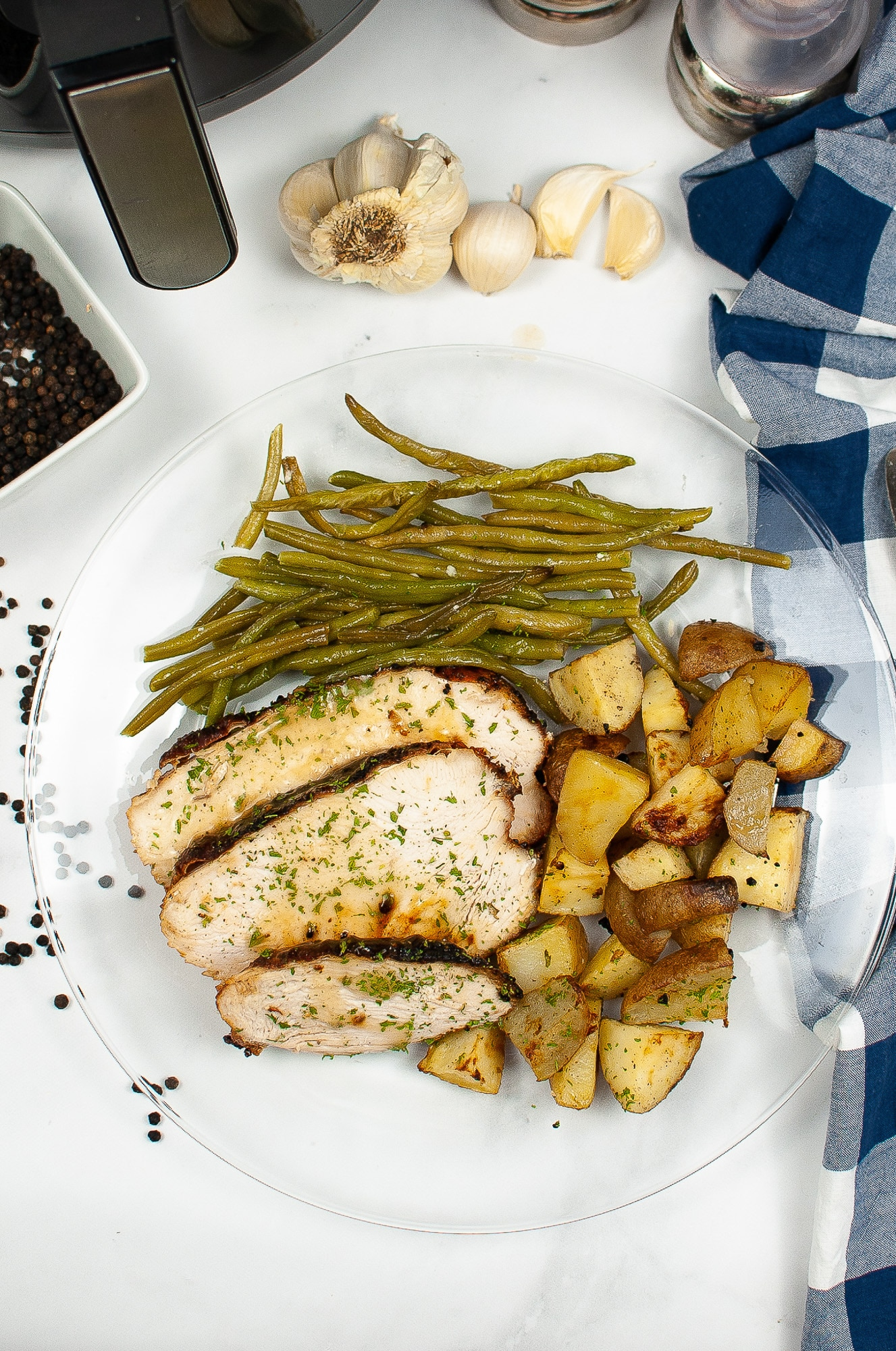 air fried turkey slices on white plate with potatoes and green beans