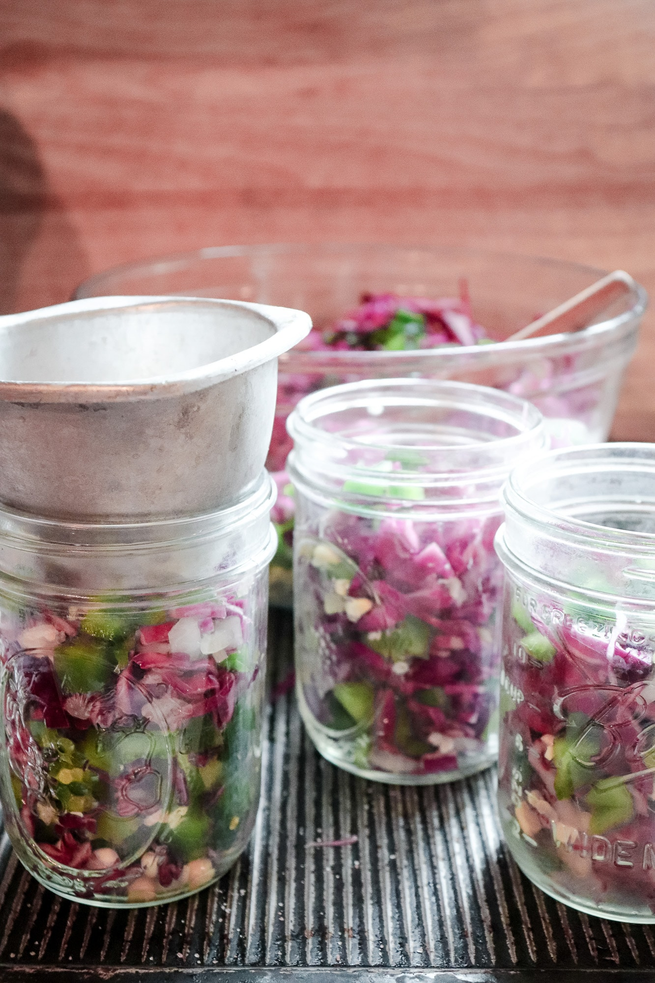 adding chopped vegetables to jars