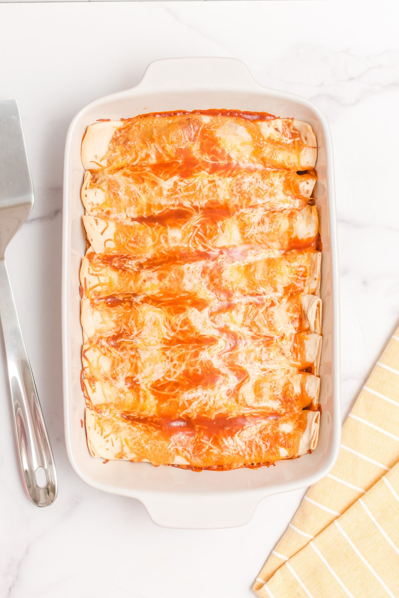 enchiladas in baking dish with some cheese