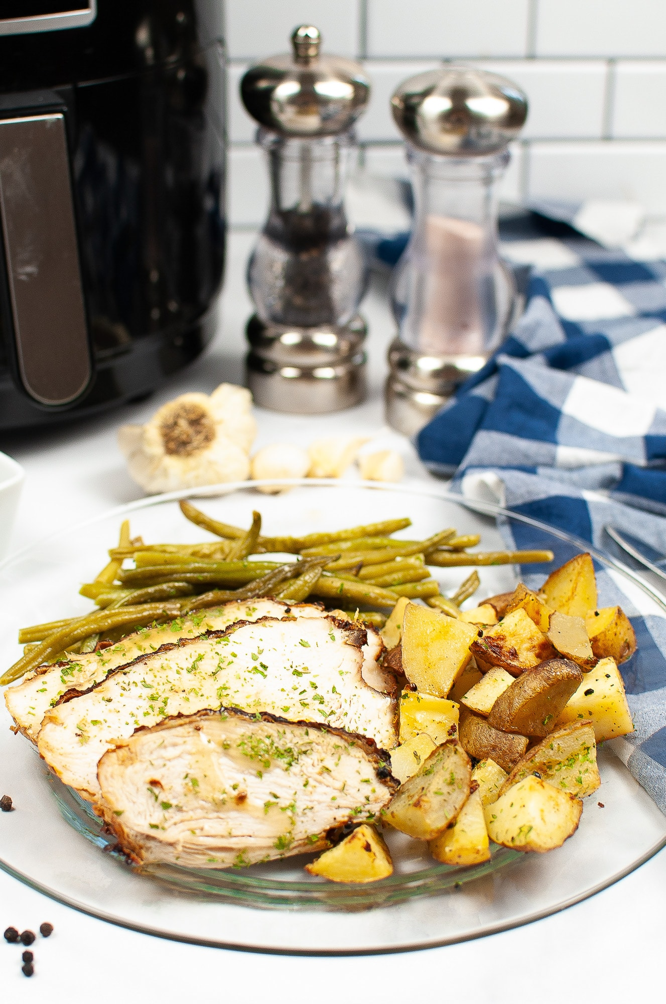 air fryer turkey breast with green beans and potatoes on white plate