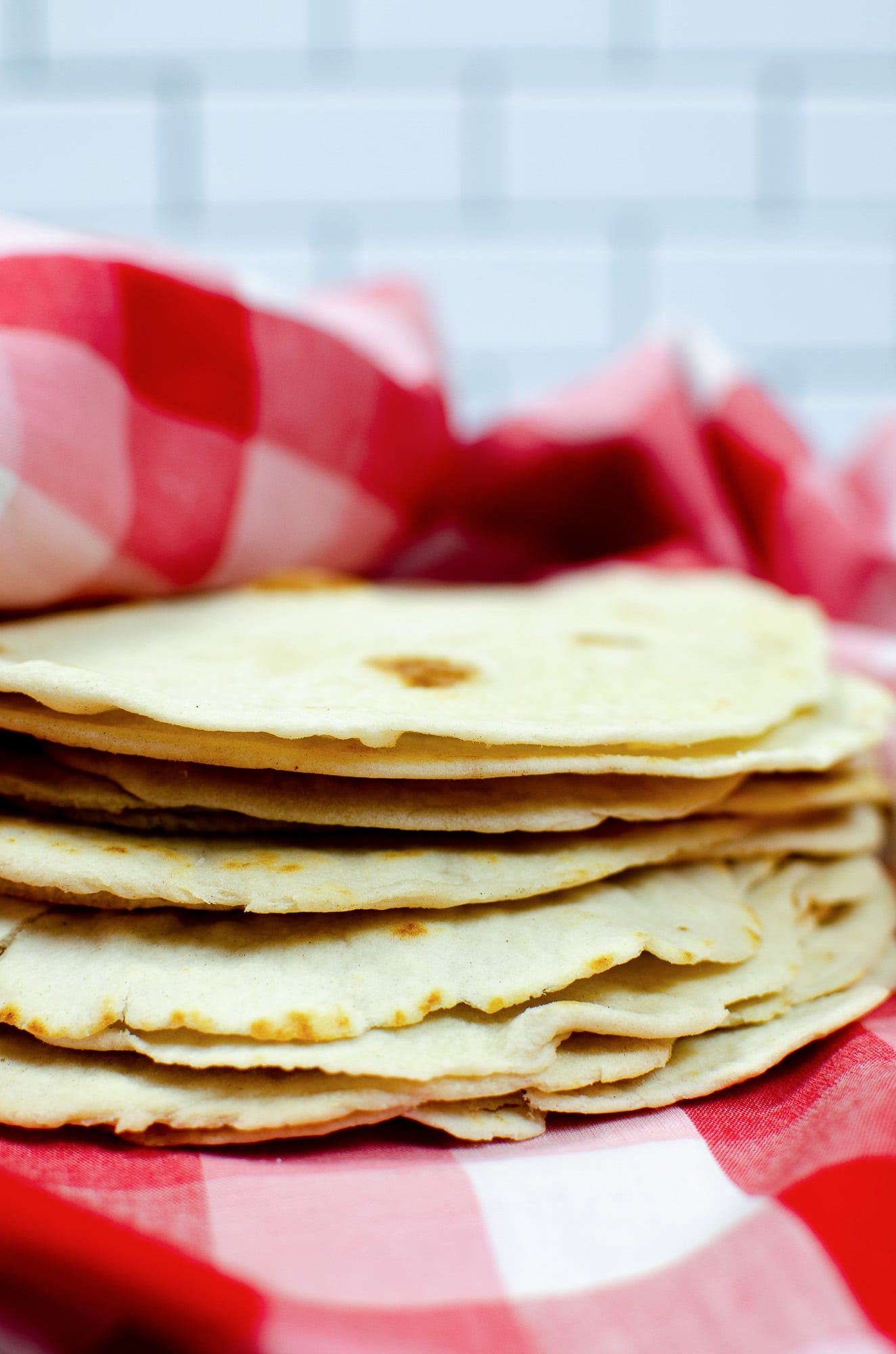 homemade flour tortillas on red and white checkered towel