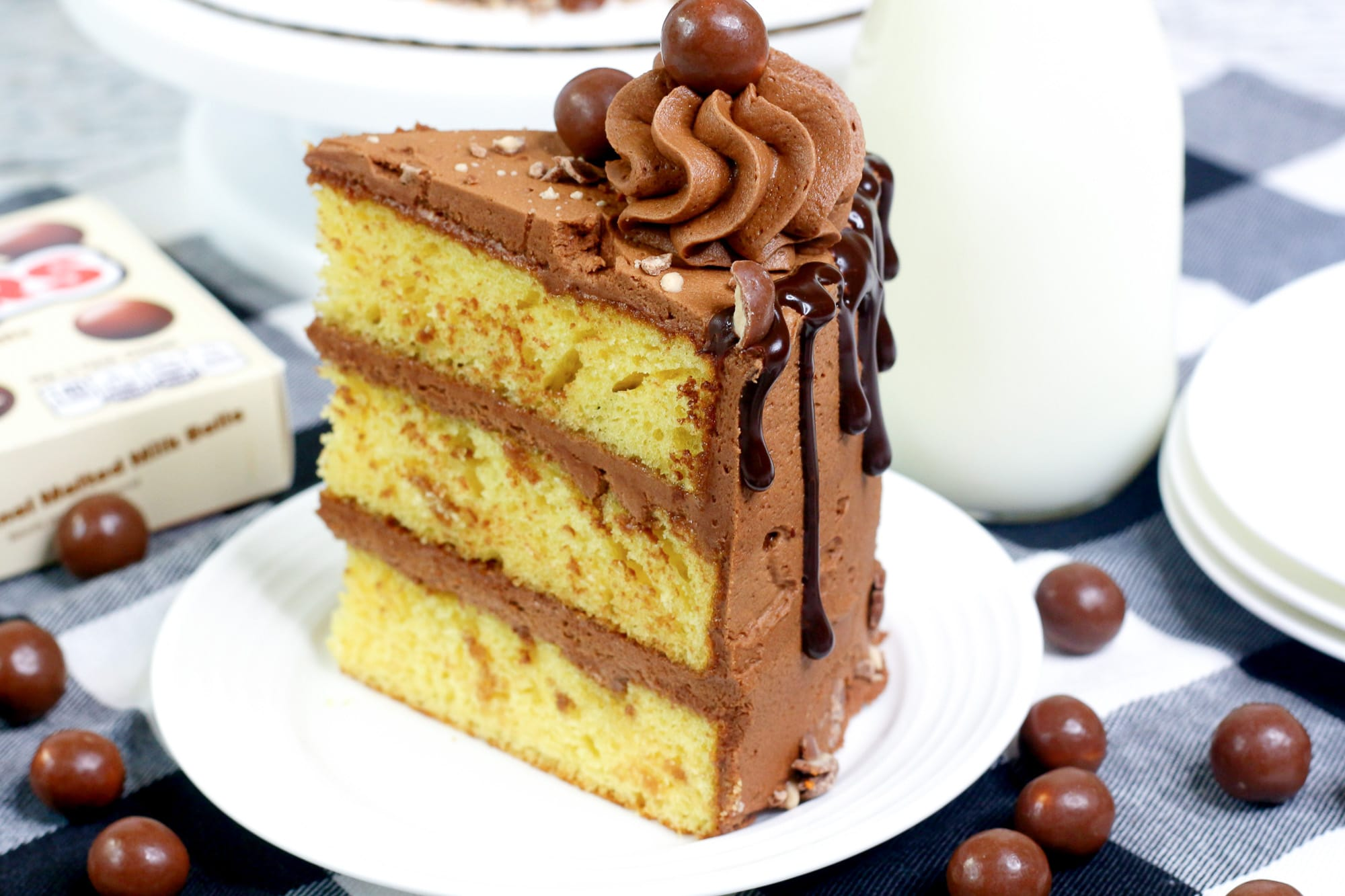 slice of butter cake with chocolate frosting on a white plate