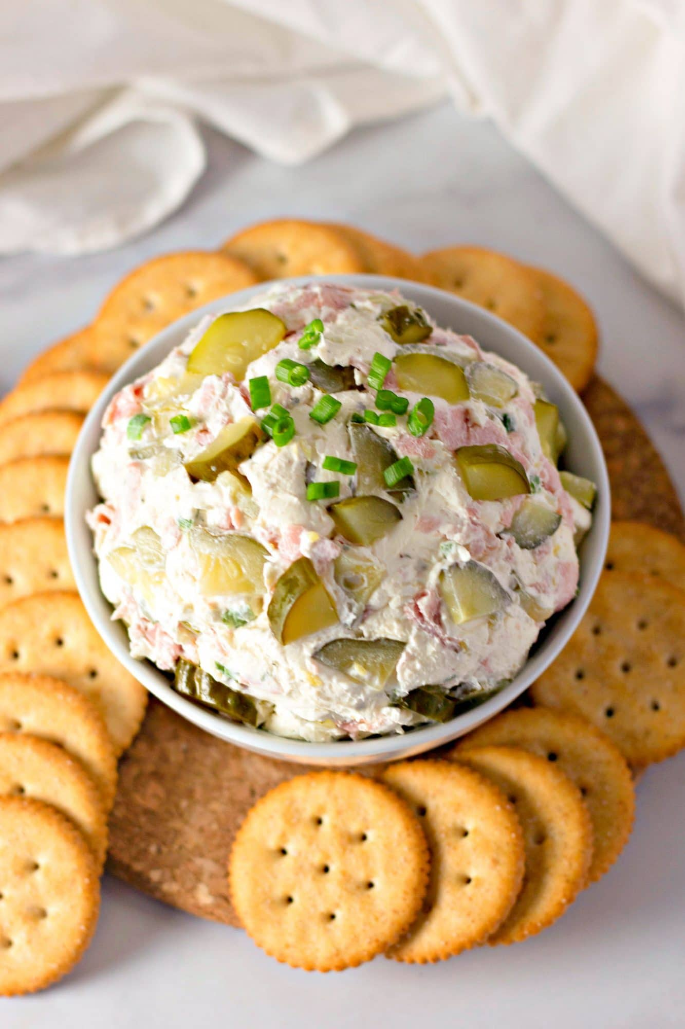 dill pickle dip in white bowl with crackers on plate